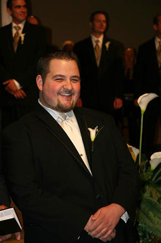 Smiling man seated, facing the camera, wearing a black tux